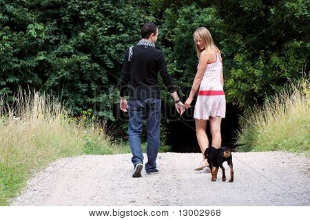 Young couple in meadow walking with dog.