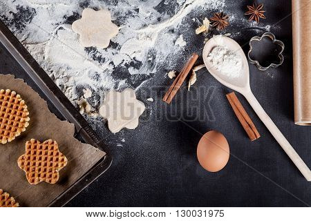 Waffle ingredients like eggs flour cinnamon anise rolling pin paper on blackboard from the top