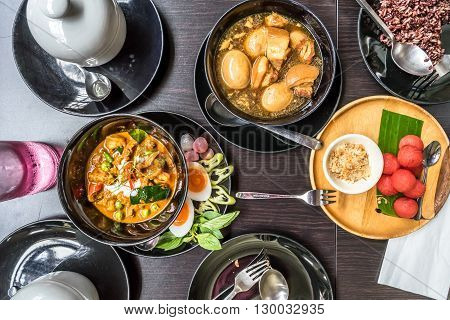 Thai Food: Flat lay of Panang (Thai Red Curry) Palo (Thai Five Spices Egg and Pork Soup) Watermelon snack and brown rice