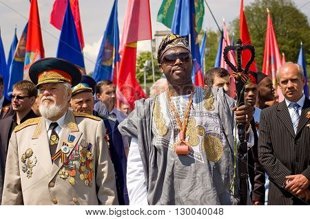 Kyiv, Ukraine - May 8, 2009: Senior Ukrainian officer and African man in traditional clothing stand in crowd during Victory Day celebration at the Museum of The History of Ukraine in World War II in Kyiv