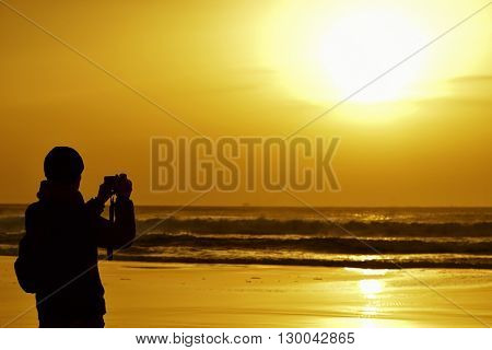 the silhouette of a young caucasian man wearing scarf and knit cap taking a picture in front of the sea at dusk, against a colorful orange sky