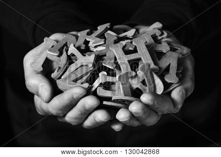 closeup of the hands of a young man holding a handful of different wooden letters, against a black background, in black and white
