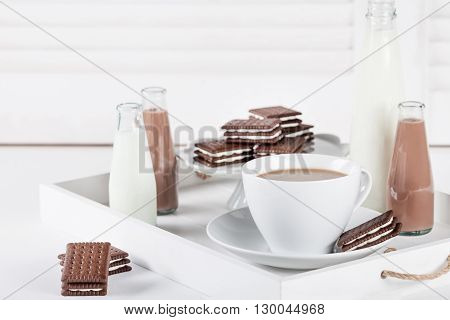 Cup of coffee and few bottles of milk and chocolate milkshakes on a white tray on white shutters background