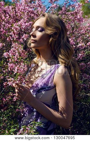 young girl a pink little flowers of almond tree Amygdalus  in Sunny day