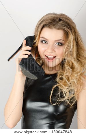 Young Amazed Woman Using Shoe Like A Telephone
