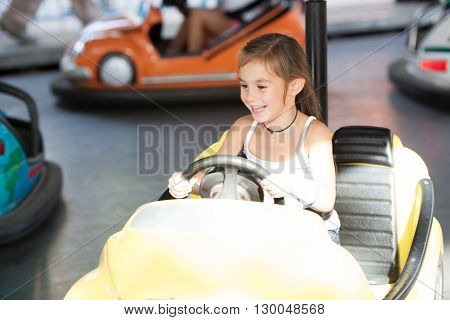 Happy child rides electric car during fan-fair entertainment