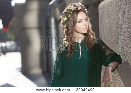 Young lovely woman with a nice flower circlet posing against sun flare.