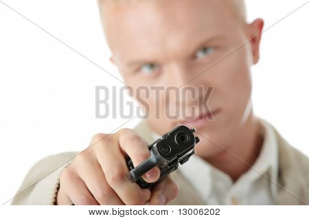 Young caucasian blond man aiming with pistol in hand