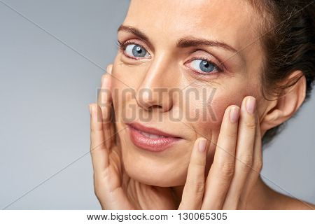 Attractive woman touching her face, mature beauty concept