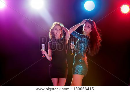 Party, holidays, celebration, nightlife and people concept - smiling young beautiful girls dancing in club