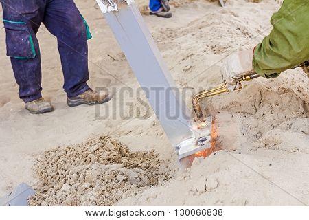 Metalworker is increasing holes diameter using metal torch. Worker is using acetylene torch to cut through metal in metalwork.