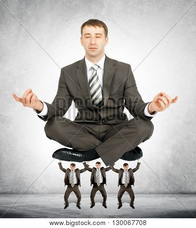 Giant businessman sitting in lotus posture on little men
