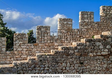 Defensive wall of the Sesimbra castle with the wall walk, crenelation and merlons, Portugal.
