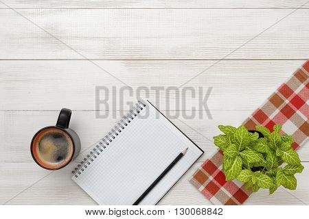 Office workplace with green houseplant on checkered tablecloth, cup of coffee and empty notebook. Top view composition. Improving mood and productivity. Increasing productivity in the mornings. Willingness to work overtime. Keeping healthy. Contribution t