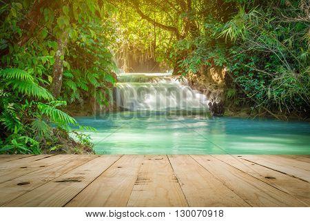 Wood table and Kuang Si waterfalls in Luang Prabang Laos.