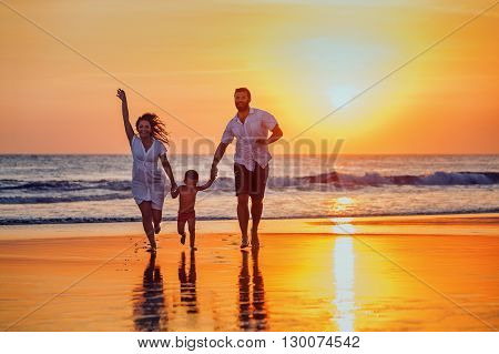 Happy family - father mother baby son hold hands and run with fun along sunset sea surf on black sand beach. Active parents and people outdoor activity on tropical summer vacations with children.