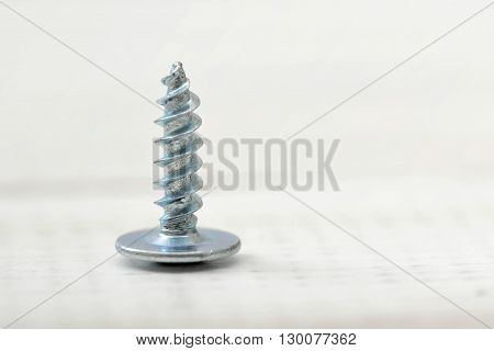 Close-up screw on wooden surface. Type of fastener. Detail with external thread.  Sheet metal screw. Mend and repair. Construction detail.