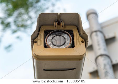 Close-up detail of a CCTV surveillance camera recording people