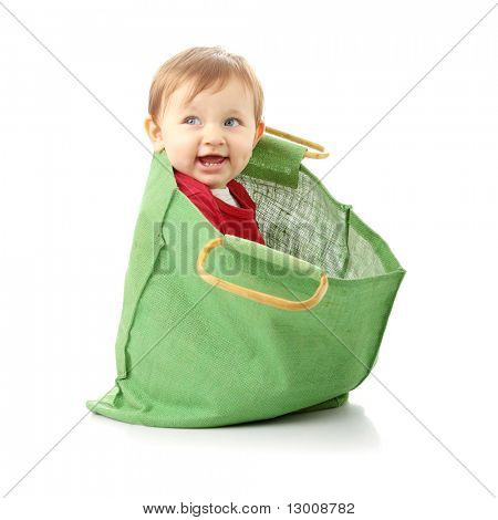 Baby girl in shopping bag, isolated on white