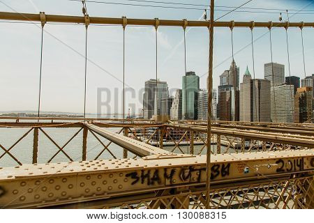 NEW YORK, USA - APRIL 21, 2016: View of New York City from the Brooklyn Bridge. The Brooklyn Bridge is a hybrid cable-stayed/suspension bridge in New York City and is one of the oldest bridges in the USA.