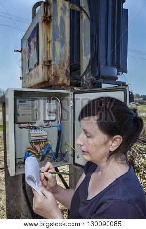 Woman electrician engineer inspecting electric counter equipment in distribution fuse box electricity switchgear power transformer substation outdoors.