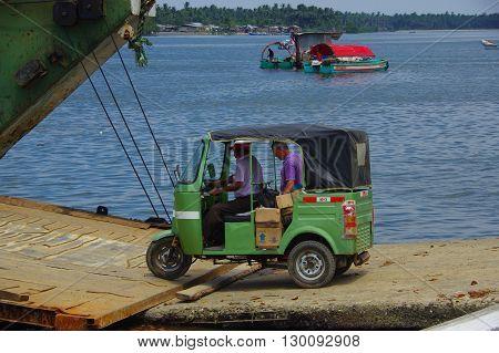 Muisne, Ecuador - March 16, 2016: Green traditional tuktuk transportation vehicle entering ferry from Muisne pier .