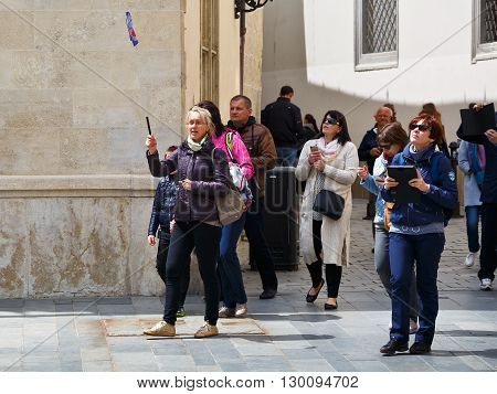 BRATISLAVA, SLOVAKIA - MAY 16, 2016: Tourist guide and a group of foreign tourists in the old town of Bratislava on May 16, 2016.