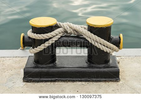 Bollard on a wharf. Ship's rope may be secured to bollard.