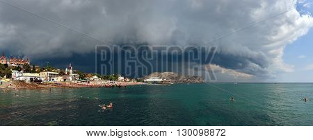 SUDAK, RUSSIA - JULY 03: Holidayers are visiting beach of resort during thunderstorm is approaching to coast on July 03, 2015 in Sudak town, Crimea, Russia.