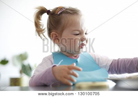 Little girl toddler picking her food making faces. Childhood problems picky eater eating habits terrible two concept.