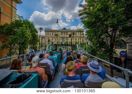 ROME, ITALY - JUNE 13, 2015: Turists bus visiting the most important places in Rome city, people watching from their seats. Justice Palace and square