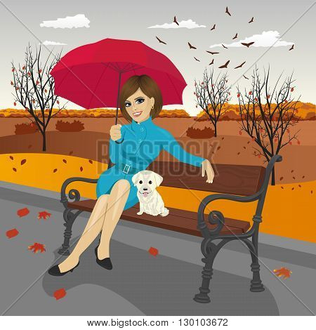 young woman in blue autumn coat holding red umbrella sitting on a bench with labrador puppy in the city park on a rainy day