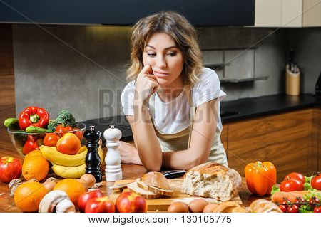 beautiful tired young lady  in the kitchen near the table with food