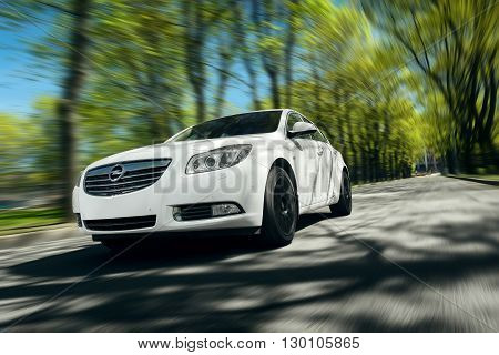 Moscow, Russia - May 07, 2015: White car Opel Insignia fast drive on asphalt road at daytime