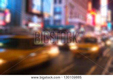 Blurred image of yellow taxi cabs driving through Times Square in New York City