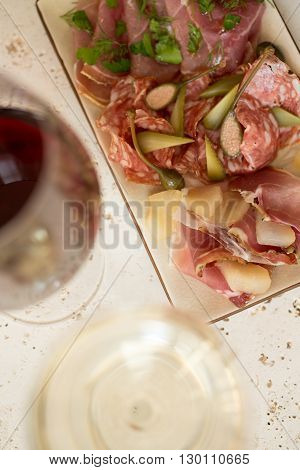 A plate of various deli meat or cold cuts and greens alongside two glasses of wine.