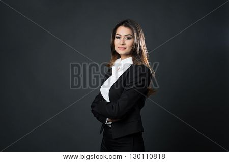 Beautiful young business woman posing on black background