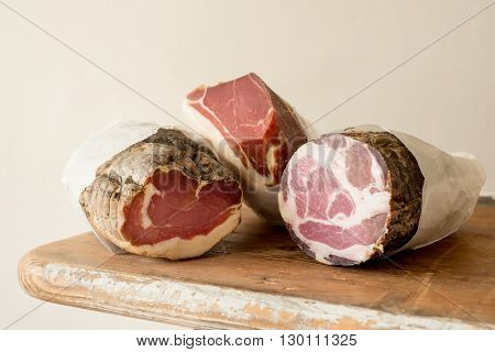 Three deli meat or cured meat logs on a wooden counter