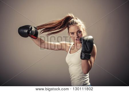 Energy fighting boxing with opponent. Sports and bodybuilding. Strong young woman punch enemy. Girl with ponytail wear white tank top and boxing gloves.