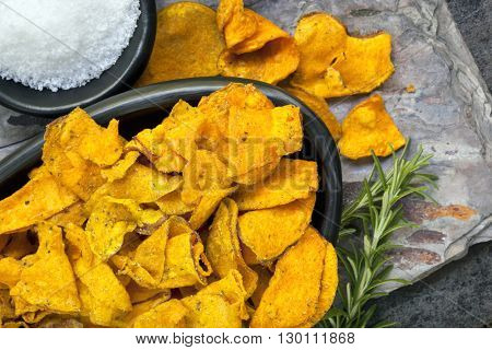 Sweet potato crisps or chips with rosemary and sea salt.  Overhead view.