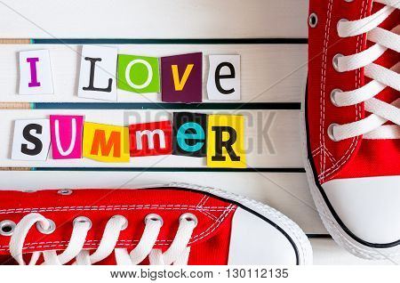 Red Gymshoes and I Love summer - written with color magazine letter clippings on wooden board. Summer vacation concept.