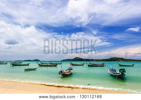 Rawai Thailand - August 25 2014: Long-tail boats for fishing & tourist trips moored in bay at Rawai beach on southern tip of Phuket southern Thailand