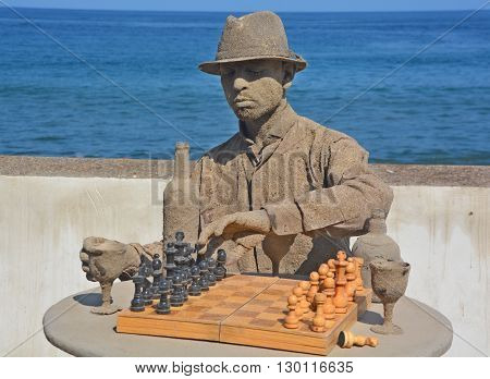 PUERTO VALLARTA MEXICO MAY 07 2016: Young man cover of sand play chess game on the side of the Puerto Vallarta beach.