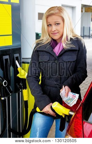 woman while refuel at petrol station