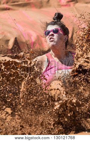HAMPTON, GA - APRIL 2016:  A woman creates a huge splash of muddy water as she lands in a mud pit at the Dirty Girl Mud Run obstacle course event in Hampton GA on April 23 2016 .