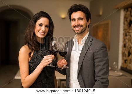 Smiling couple toasting wineglasses