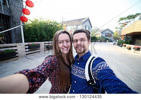 A loving couple traveling makes selfie. Free travelers. Work online.
