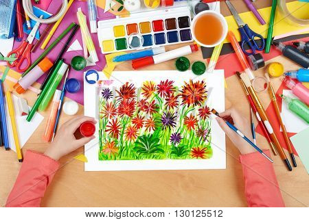 flower bed meadow closeup background, child drawing, top view hands with pencil painting picture on paper, artwork workplace