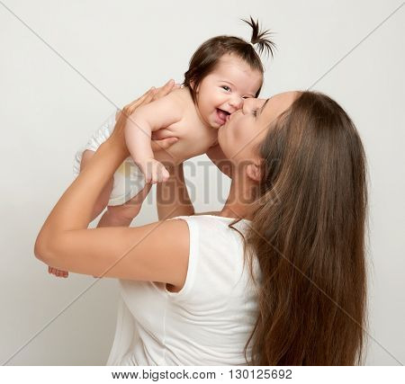 Mom throws up baby and kiss, play and having fun, parenting, happy family concept
