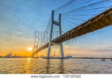 Ho Chi Minh city, Vietnam - January 14th, 2016: Sunset Phu My bridge with steel wire radiating sun rays under bridge highlighting beauty connecting two banks on Saigon River Ho Chi Minh City, Vietnam